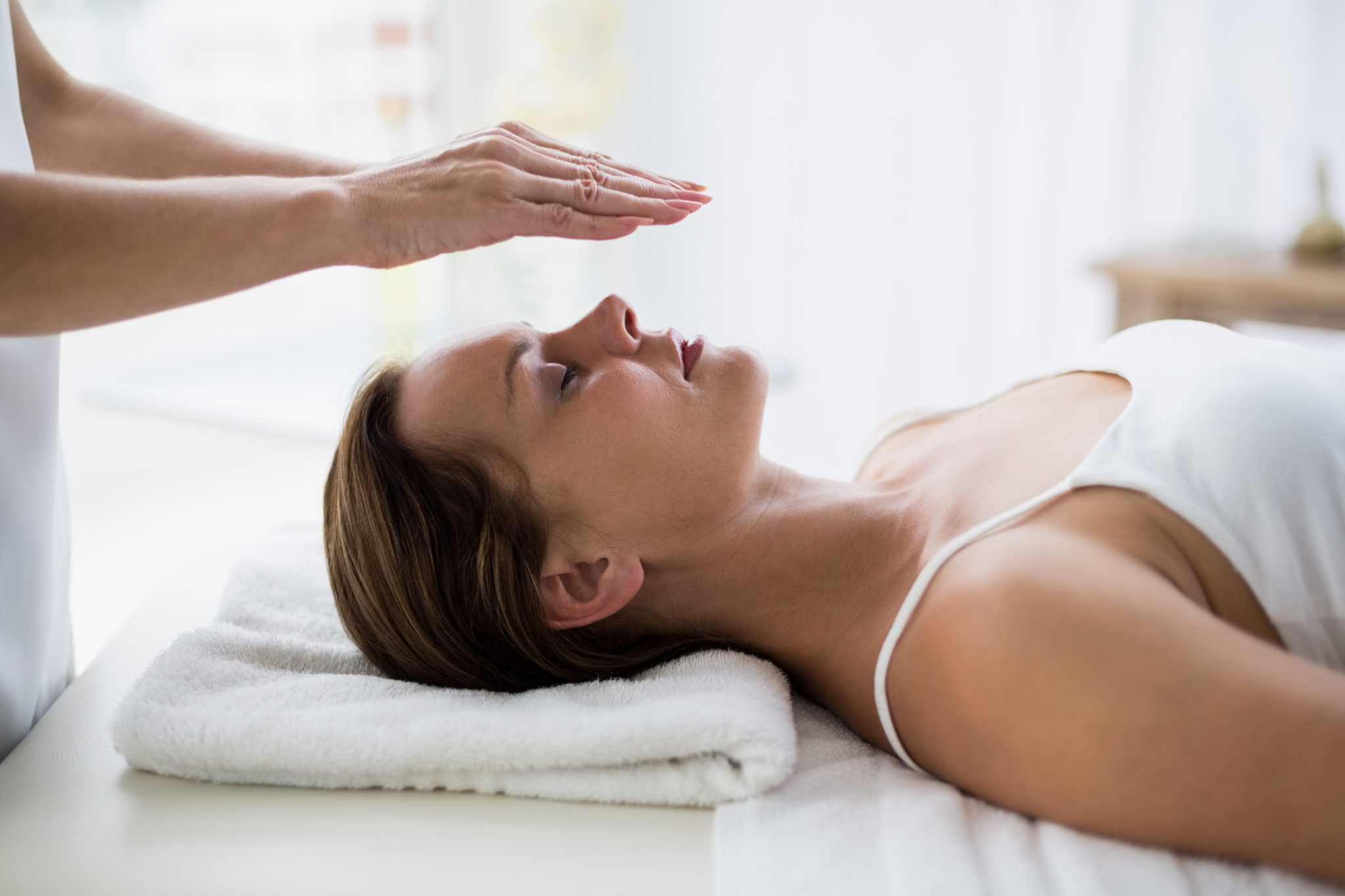 Therapist performing reiki on woman's head